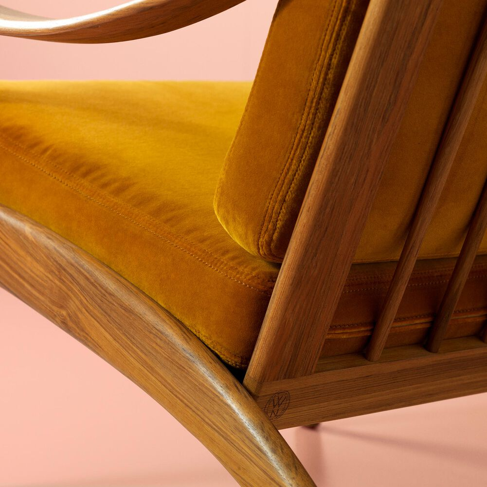 Close-up of Lean Back lounge chair in teak wood and amber velvet.