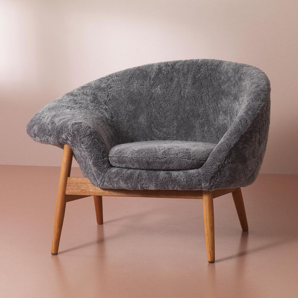Fried Egg lounge chair in Scandinavian grey wool on a pink background.
