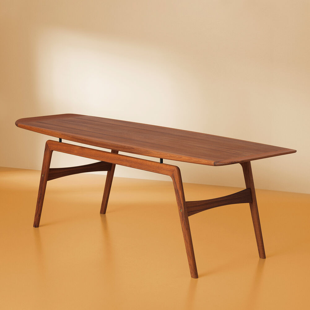 Surfboard coffee table in teakwood on coloured background.