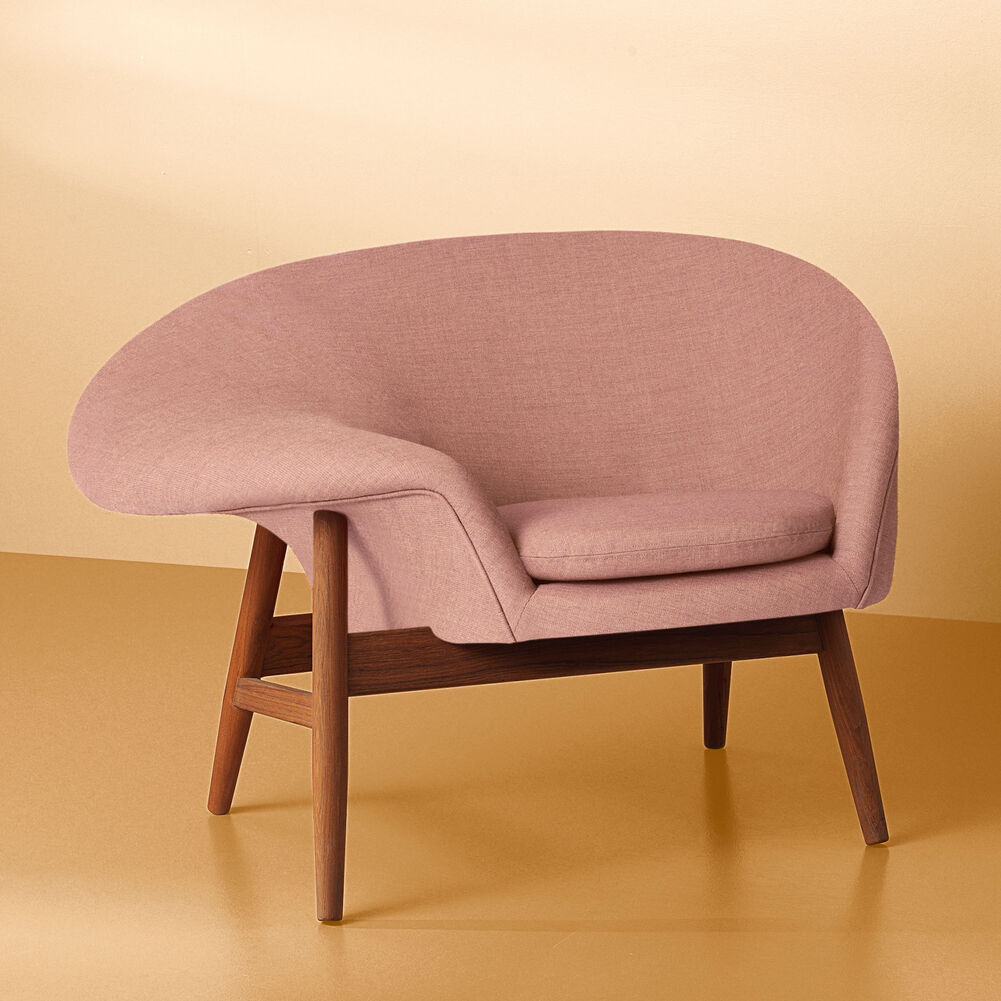 Fried Egg lounge chair in pink on a yellow background.
