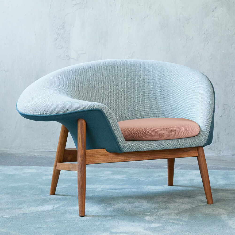Fried Egg lounge chair in light green, blue petrol and fresh peach colour in a light room.