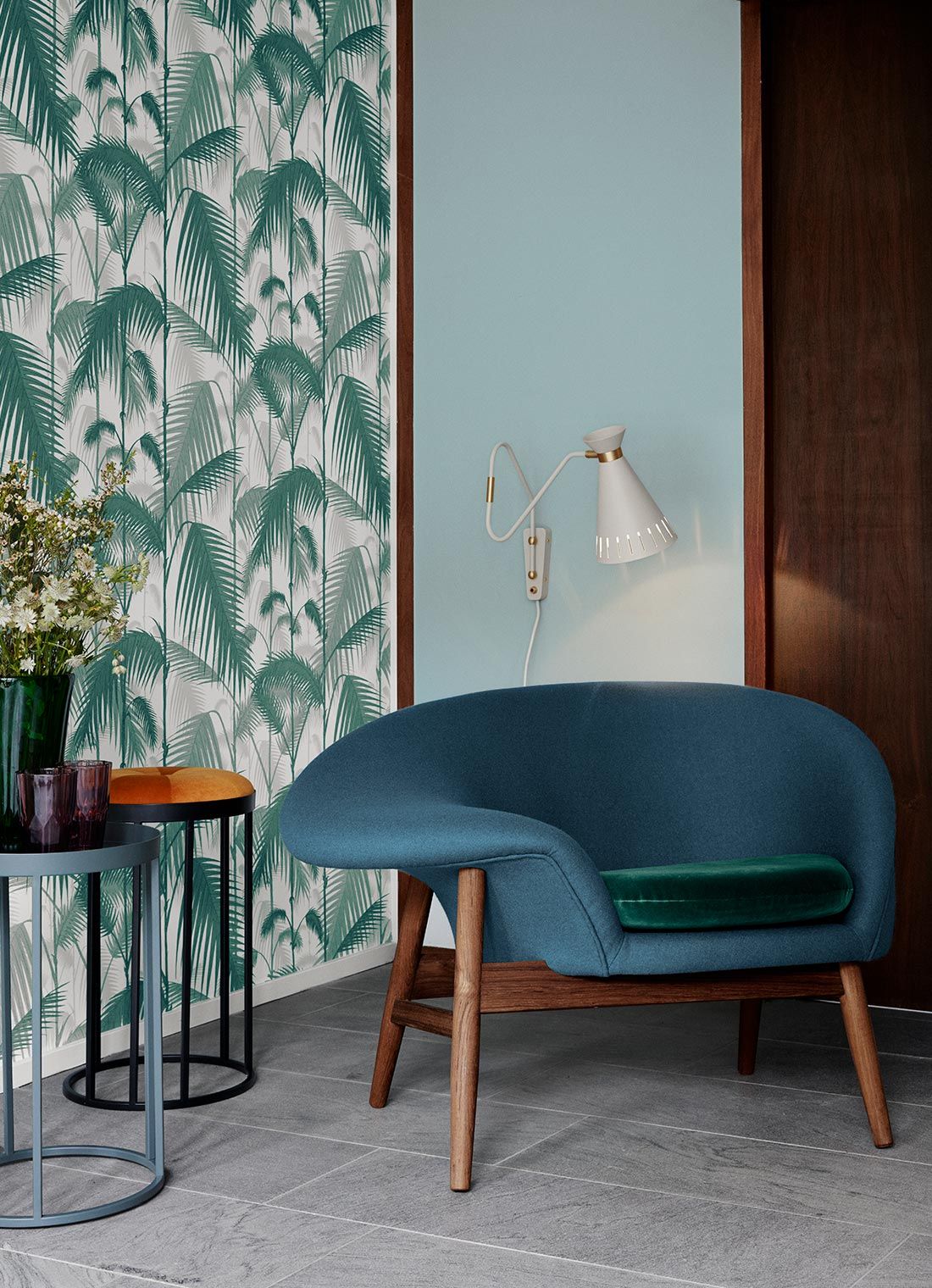 Fried Egg in blue petrol with a green velvet cushion next to Daisy stools and Cone wall lamp.