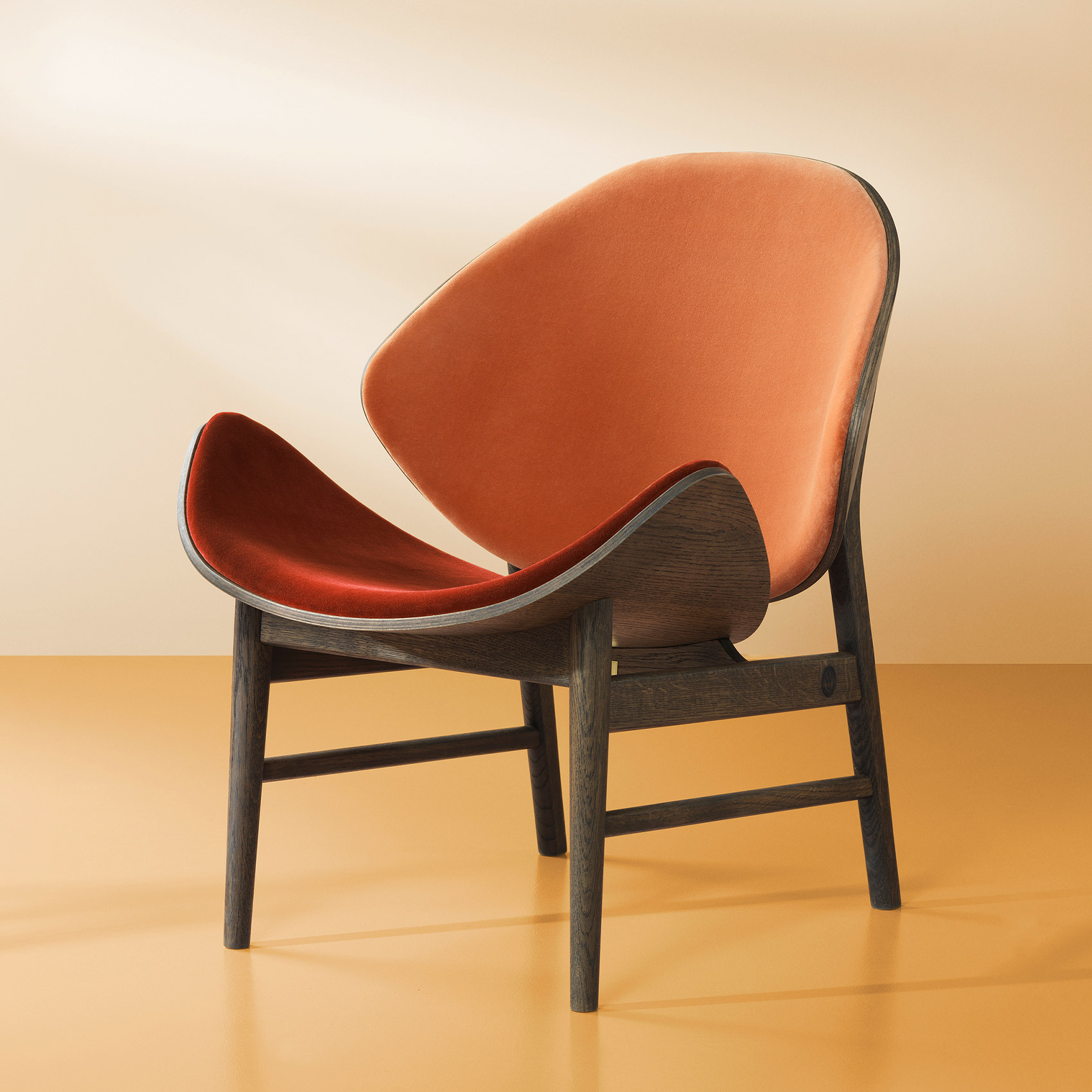 The orange lounge chair in smoked oak and rusty rose/brick red colour