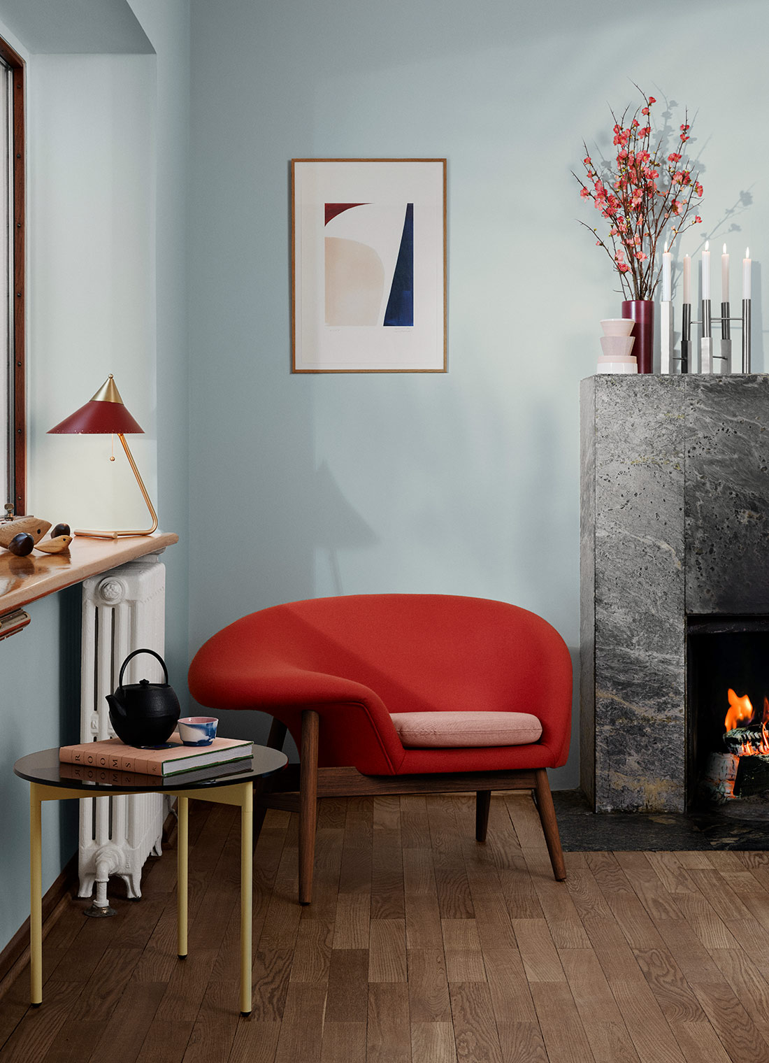 Red Fried Egg chair by the fireplace in a nicely decorated room.