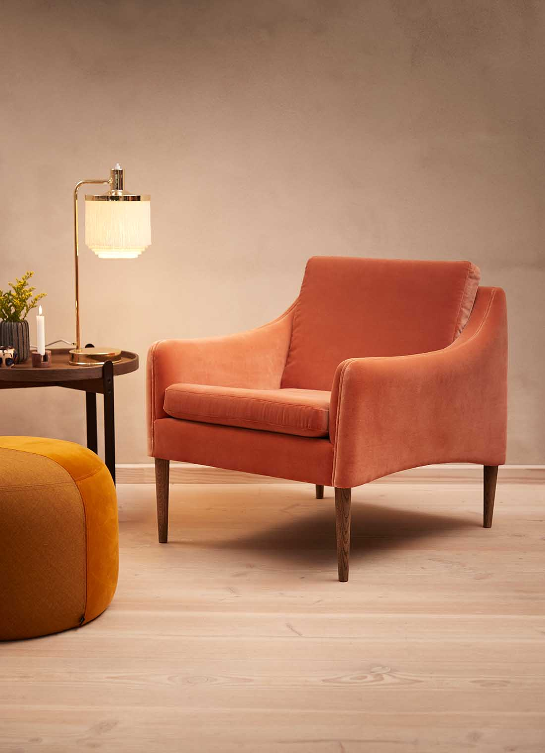 Mr. Olsen lounge chair in rusty rose velvet with a table and a pouf.
