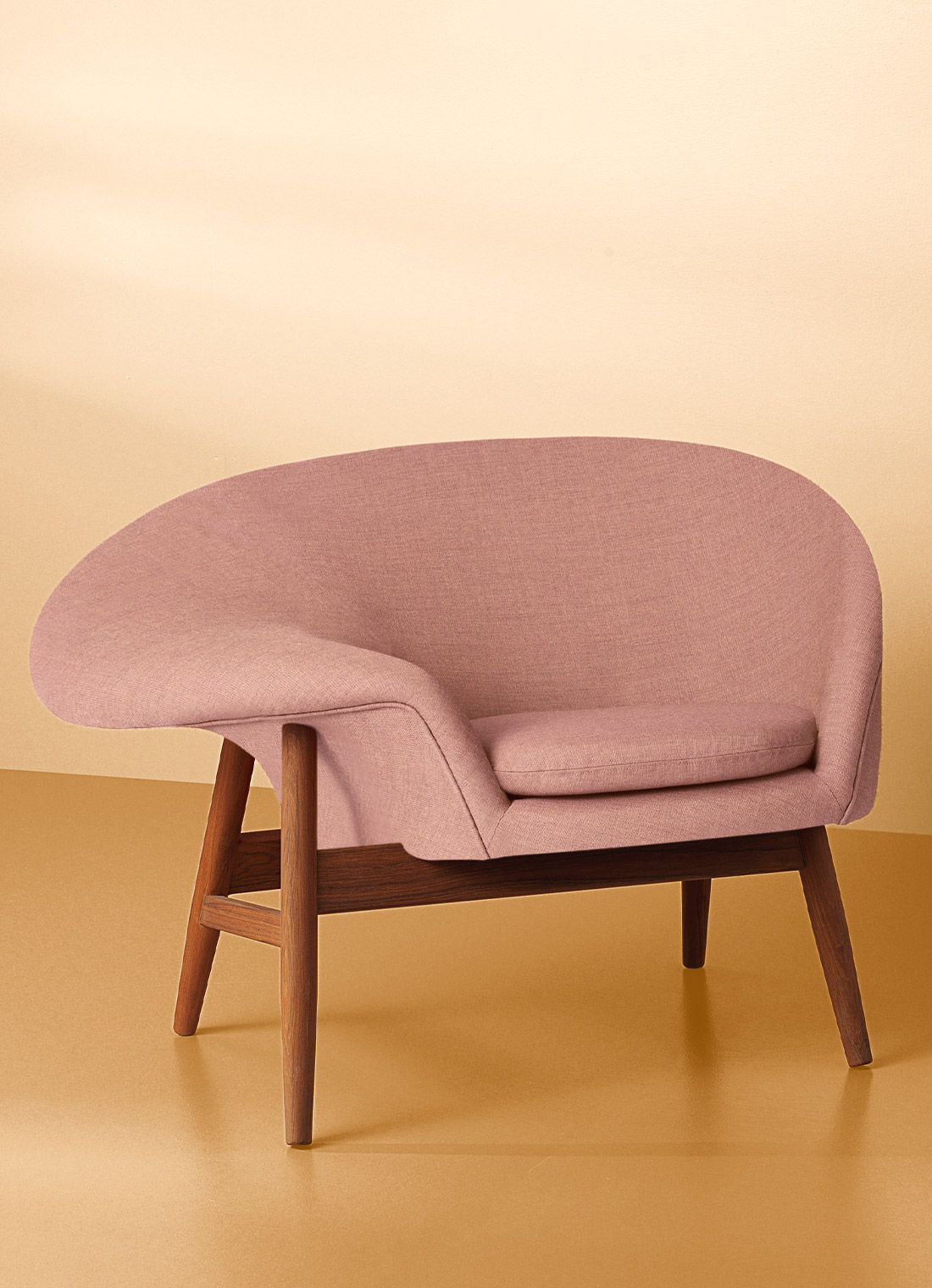 Fried Egg lounge chair in pale rose colour on yellow background.